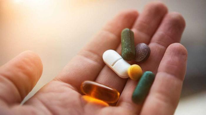 таблетки, капсулы в руке